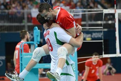 Bulgaria's Teodor Salparov celebrates victory with an unidentified player in the Men's Preliminary Pool A volleyball match between Poland and Bulgaria in the 2012 London Olympic Games in London on July 31, 2012. AFP PHOTO/KIRILL KUDRYAVTSEVKIRILL KUDRYAVTSEV/AFP/GettyImages