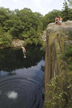 Jake Peverada, of Beverly, jumped from a cliff at Nelson's quarry in Gloucester Wednesday while Brian Day, of Danvers, and Hanna Longwell, of McLean, Va., watched.