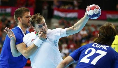 Hungary's Gabor Csaszar took a shot against Croatia's Drago Vukovic, left, and Ivan Cupic in their men's handball Preliminaries Group B match.