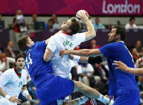 Hungary's Gabor Csaszar took a shot challenged by Croatia's Drago Vukovic, left, in the men's handball Preliminaries Group B match.