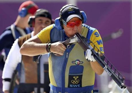 Sweden's Hakan Dahlby blew into his shotgun during the men's double trap shooting finals.