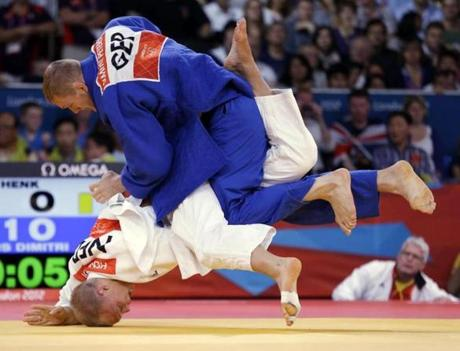 Henk Grol of the Netherlands competed against Dimitri Peters of Germany (in blue) during the men's 100-kg judo competition.
