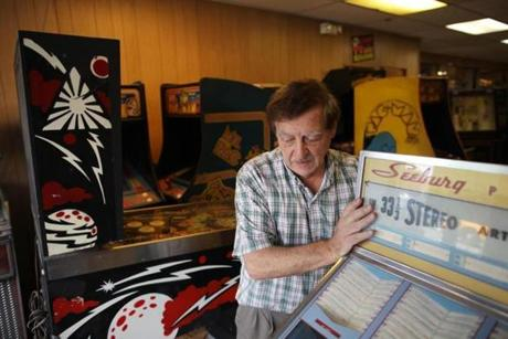 David Garnick moves a restored 1960s-era Seeburg jukebox through the front of his store in Lowell.