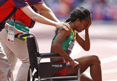 Ethiopia's Genzebe Dibaba is helped off the track after injuring herself in a women's 1500-meter heat during the athletics in the Olympic Stadium at the 2012 Summer Olympics, London, Monday, Aug. 6, 2012. (AP Photo/Daniel Ochoa De Olza)