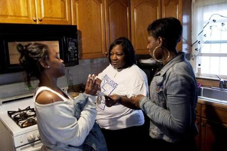 Theresa Johnson, center, speaks with daughter, Ceecee, left, and her granddaughter's mother Tricia Ariol, right, while preparing lasagna at her home in Dorchester on  June 13.