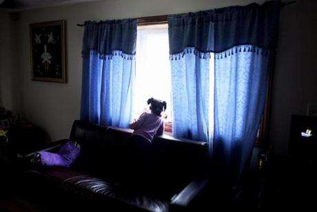 Trinity Dale-Johnson, granddaughter of Theresa Johnson, looks out the window of Johnson's home in Dorchester on June 13.