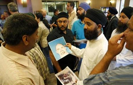 Members of the Sikh community held up the mug shot handed out by the FBI of the suspected shooter Wade Michael Page.