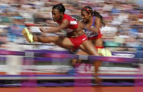 Kellie Wells of the U.S. (L) and Colombia's Lina Florez compete in their women's 100m hurdles round 1 heat during the London 2012 Olympic Games at the Olympic Stadium August 6, 2012. REUTERS/Phil Noble (BRITAIN - Tags: SPORT ATHLETICS OLYMPICS)