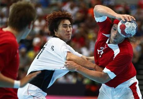 South Korea's Jung Suyoung (L) challenges Denmark's Mikkel Hansen in their men's handball Preliminaries Group B match at the Copper Box venue during the London 2012 Olympic Games August 6, 2012. REUTERS/Marko Djurica (BRITAIN - Tags: SPORT HANDBALL OLYMPICS)
