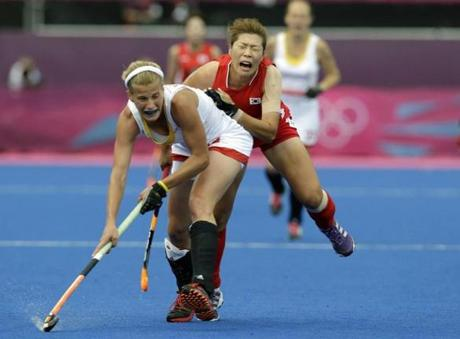 South Korea's Kim Young-ran, right, and Belgium's Gaelle Valcke, left, fight for the ball during a preliminary round women's field hockey match at the Riverside Arena at the 2012 Summer Olympics, London, Monday, Aug. 6, 2012.(AP Photo/Lefteris Pitarakis)