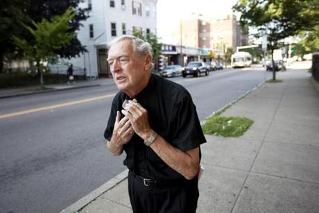 Father Doc Conway of St. Peter Church put on his clerical collar as he started his evening walk in the Bowdoin- Geneva neighborhood on July 8. Maria's edit: Father Doc Conway of St. Peter's Church put on his clerical collar as he started his evening walk in the Bowdoin- Geneva neighborhood on July 8.