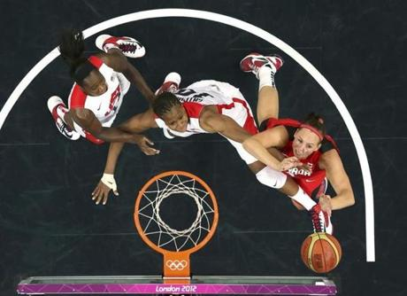 Canada's Krista Phillips (R) reaches for the rebound with Tamika Catchings (C) and Tina Charles (L) both of the U.S. in the women's quarterfinal basketball match at the Basketball Arena in London during the London 2012 Olympic Games August 7, 2012. REUTERS/Mike Segar (BRITAIN - Tags: SPORT OLYMPICS SPORT BASKETBALL)