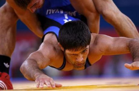 Iran's Saeid Morad Abdvali (in blue) fights with France's Steeve Guenot on the Men's 66Kg Greco-Roman wrestling at the ExCel venue during the London 2012 Olympic Games August 7, 2012. REUTERS/Damir Sagolj (BRITAIN - Tags: OLYMPICS SPORT WRESTLING)