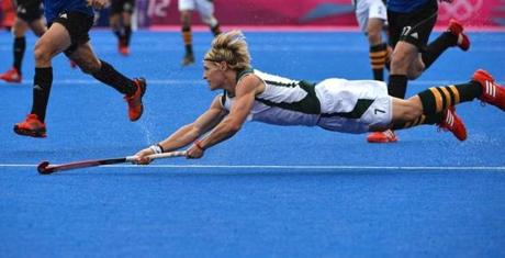 Timothy Drummond of South Africa dives to pass a ball during the field hockey preliminary round match between Argentina and South Africa at the Riverbank Arena in London on August 7, 2012, during the London 2012 Olympic Games. AFP PHOTO/ INDRANIL MUKHERJEEINDRANIL MUKHERJEE/AFP/GettyImages