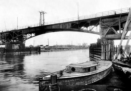December 31, 1926: The Bourne Highway Bridge over the Cape Cod Canal opened in May 1911. The limitations of the narrow horizontal and vertical clearance — even with the sides in the upright position — made navigation challenging. It was the site of frequent ship collisions. On June 23 1935, the new Bourne Bridge opened and the old Sagamore bridge continued in use until midnight of the same day. Work of razing the old bridges began the next morning.