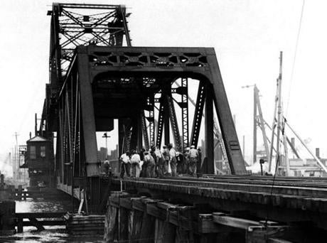 July 21, 1943: An emergency crew of 75 men worked on the Buzzards Bay railroad bridge after an oil barge bound from Boston to Bridgeport with 4,500 gallons of gasoline rammed the bridge side-on to lift the whole structure several inches. The oil barge signaled for the draw just about dawn. When the bridge did not open on signal, the barge could not stop against the current and rammed the truss. The failure of the draw to open was blamed on excavation for the new railroad bridge across the canal, which caused some slight settling of the old bridge.