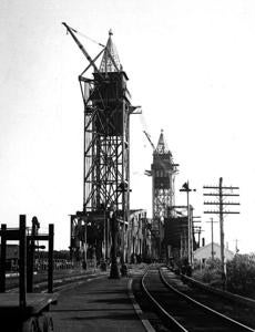 September 20, 1935: Work neared completion on the new Railroad Bridge over the Cape Cod Canal. The bridge weighed 2000 tons and carried a single rail track. At the time of its opening on December 29, 1935, the new bridge had the longest span of any vertical lift bridge in the United States. This span of 544 feet hung suspended from the two 265-foot-tall towers, with its lower rail 135 feet above the canal at low tide. When a train crosses, the span is lowered into place. At all other times, it hangs high above the waterway permitting ships to pass through.