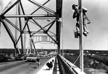 May 28, 1970: Bridge painting freshened up the Sagamore Bridge for the upcoming summer season. While the worker in the foreground hung from a precarious looking pulley system, the man in the background appeared unattached as he worked high over the passing traffic underneath. The boys and their dogs made their way on the less busy side of the roadway.