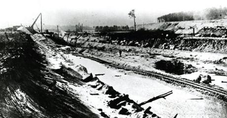 January 1910: The first excavation work on the proposed Cape Cod Canal began on the Scusset marshes at a point about a half mile from the shores of Cape Cod Bay. The steam excavator, seen in the distance, that began the work was brought there in sections and it required more than a month to set up the big machine.