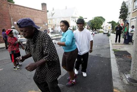 Susan Young dances with Bobby Clark (right) and another man during a block party on Norton Street on July 20.