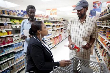 Susan Young helps Antonio Walker (right) do his grocery shopping while a longtime friend of Walker's, Donald