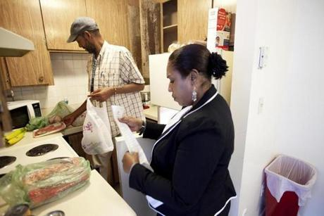 Susan Young helped Antonio Walker arrange his groceries in his new apartment.