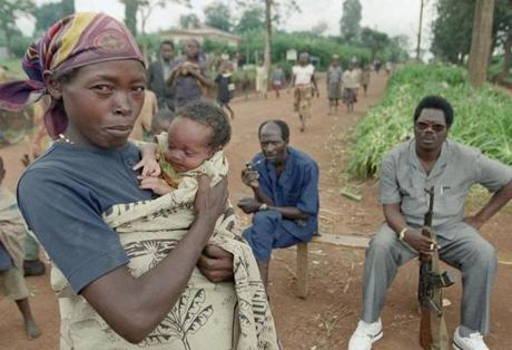 A woman and her baby walked by a militiaman armed with an AK 47 automatic rifle in Butare, Rwanda, in June, 1994.