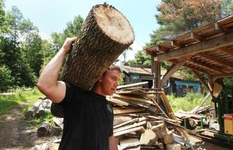 Jesse LaCasse carries a piece of an ash tree he has cut down over to the sawmill to be further cut.