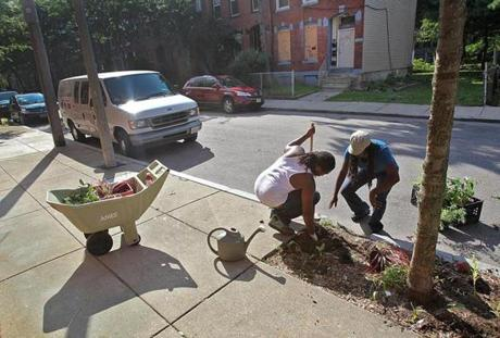 After weeks of work to bring her street and her neighbors together, Jhana Senxian, was finally ready in August to plant flowers on the sidewalks of Coleman Street. She worked alongside Donald Aaron.