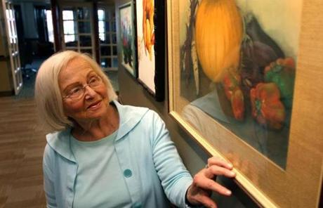Sylvia Namyet, 88, stood with one of her watercolor paintings that is on display in the lobby at the Orchard Cove residence.