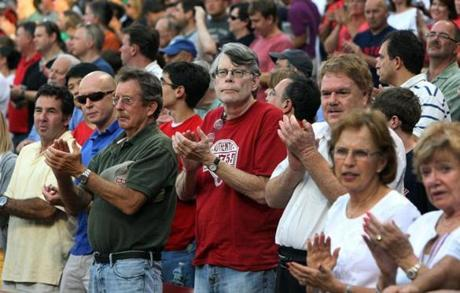 8-21-2012: Boston, MA: Author Stephen King (center in red shirt) was one of the fans standing and applauding during the pre game Johnny Pesky ceremony. The Boston Red Sox hosted the Los Angeles Angels in an MLB game at Fenway Park. section: sports (Globe Staff Photo/Jim Davis)