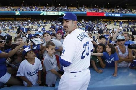 Back in California, Adrian Gonzalez signed autographs Saturday prior to the start of his first game with the Los Angeles Dodgers.
