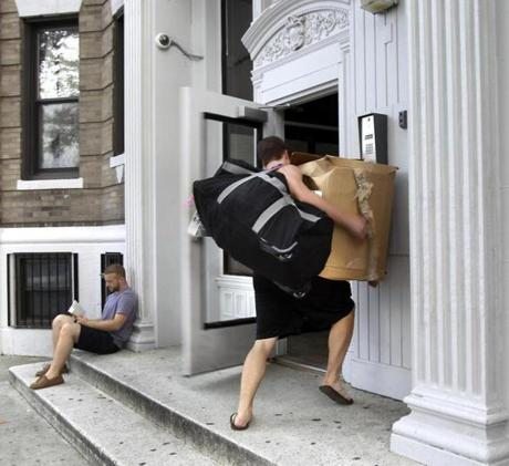 Conor Bailey struggles with a full load as he opens the door to an apartment building on Commonwealth Avenue in Boston. He was moving back in after being elsewhere for the summer, and will move again at the end of the week.