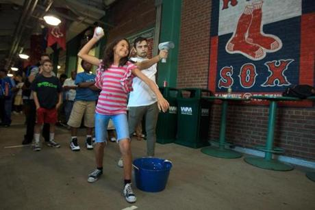 "Boston, MA - 8/28/2012 - Fenway Park - Wendy Bonilla, cq, 11, of East Boston, hurled a baseball into a net to see how fast she could throw. Bonilla will be a sixth grader at the Mario Umana Middle School Academy in East Boston this fall. Fenway Park was host to host hundreds of in-coming Boston 6th graders for the annual ""Middle O!"" event - a huge back-to-school orientation event featuring free food, information tables, games and a great view of the ballpark. Dina Rudick/Globe Staff."