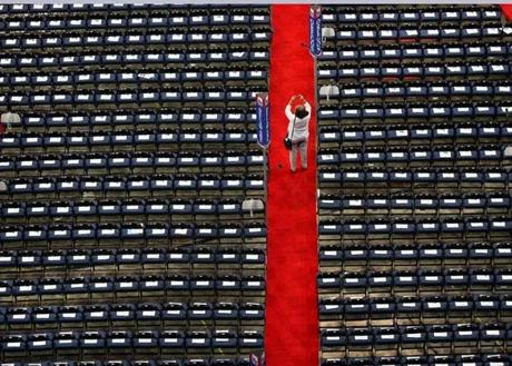A delegate takes a picture between empty seats before the start of the night.