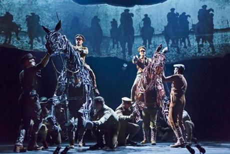 "Grayson DeJesus and Michael Wyatt Cox sit atop horses, with the puppeteers inside, during a performance of ""War Horse."""