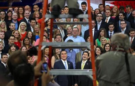 Republican presidential nominee Mitt Romney and his running mate Paul Ryan were framed through the photographer's ladder during a photo shoot of staff members before the final night of the GOP convention in Tampa, Fla. Aug. 30, 2102.