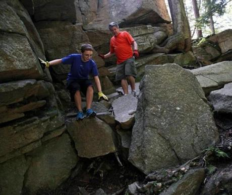 "SUTTON, MASS. -- Oct. 2, 2005 --- Jan Enkvist, (cq) 9, of Cambridge, climbs up through a crevice knows as ""Fat Man's Misery"" during a visit with his family at Purgatory Chasm State Park. --PHOTOGRAPH BY NANCY PALMIERI Library Tag 11202005 Travel - New England"