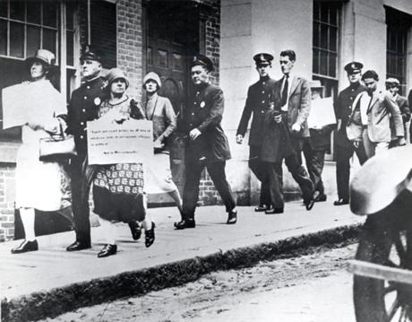August 10, 1927: The picketing of the State House by Sacco and Vanzetti sympathetic strikers culminated in the arrest of 39 picketers. Hundreds followed the officers and their prisoners as they marched down Beacon St. and turned into Joy St. to Boston Police Station 3. This woman's sign said,