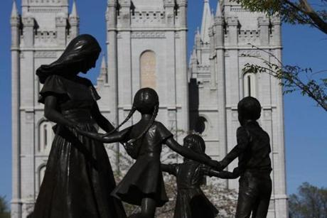 Bronze statue of mother and dancing children in front of the Salt Lake Temple on Temple Square.