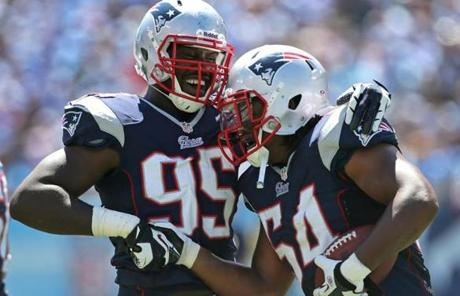 New England Patriots defensive end Chandler Jones (95) and linebacker Dont'a Hightower (54) celebrated after Hightower recovered Jones's fumble for a touchdown run during the season opener against  the Tennessee Titans at LP Field in Nashville.