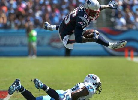 New England Patriots wide receiver Brandon Lloyd (85) hurdled Tennessee Titans cornerback Coty Sensabaugh (24) for a 6 yard gain on a third quarter drive that set up a touchdown run at LP Field in Nashville.