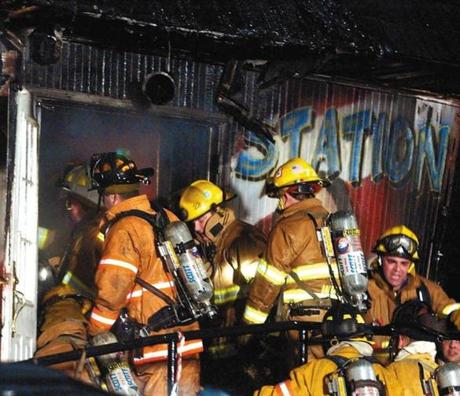 Firefighters crowded the front entrance to look for victims and try to control the fire.