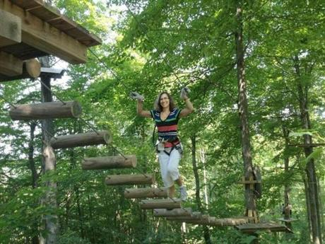 The author's wife, Lisa, on a wood-and-ropes bridge. Height and difficulty of obstacles increase with harder courses.