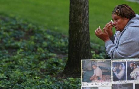 Maria Rodriguez wiped her eyes near pictures of a victim before ceremonies marking the 11th anniversary of the attacks in New York.