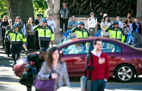 Boston Police officers and bystanders along Beacon Street listened to the National Anthem at a a State House ceremony.