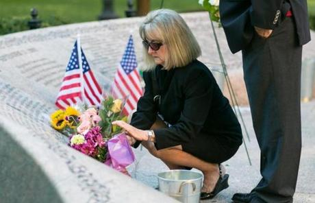 Faye Kane, who lost her 26-year-old daughter, Jennifer Kane, in the attacks, flowers at the memorial at the Boston Public Garden.