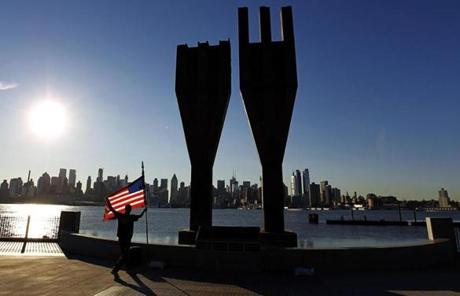 A man placed a US flag next to a memorial bearing two pieces of steel from the World Trade Center in Weehawken, N.J.