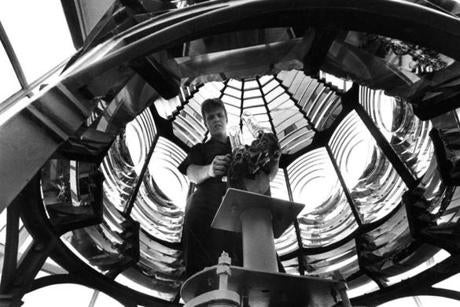 August 26, 1984.  Coastguardsman Patrick Doherty adjusts the lighhouse lamp while standing in the middle of the second-order Fresnel lens imported from France in 1859. The assembly is 11 feet tall, comprised of 336 individual prisms with 12 bullseyes. The light Doherty is cleaning is a 1,000 watt lamp, magnified to 2,000,000 candle power by the Fresnel lens that's visible for 27 nautical miles on a clear night. The second lamp is for backup.
