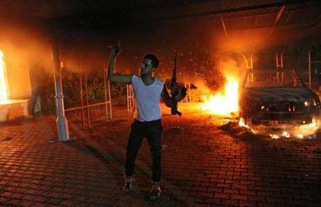 An armed man was seen at  the US consulate in Benghazi, Libya, Tuesday as buildings and vehicles burned.